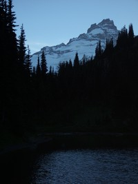 dark mt rainier behind lake