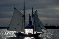 sailing ship in front of Statue of Liberty